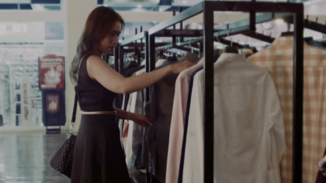 woman choosing clothes in the mall - clothing store stock videos & royalty-free footage