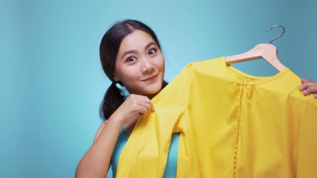 vidéos et rushes de femme en choisissant des vêtements sur fond bleu isolé 4k - rangement