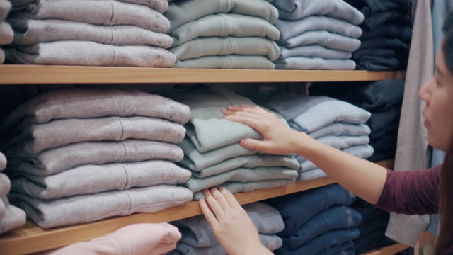 woman choosing clothes on shelf at clothes shop - t shirt stock videos & royalty-free footage