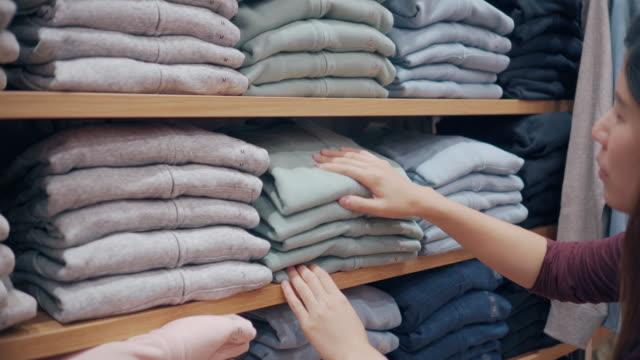 vídeos de stock, filmes e b-roll de mulher escolhendo roupas na prateleira da loja de roupas - vendendo