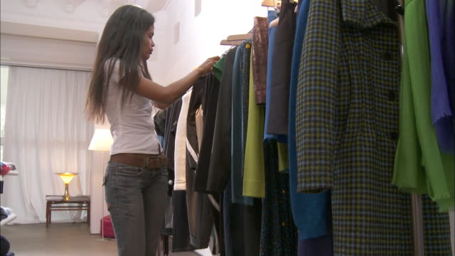 ms woman choosing dress from clothes rack / brussels, belgium - clothes shop stock videos and b-roll footage