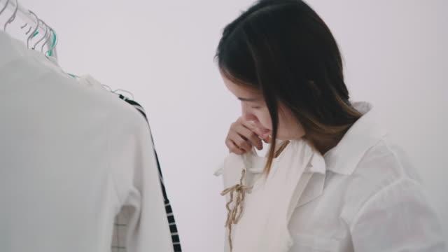 Kvinnan att välja klänning från rack med galgar inuti rummet