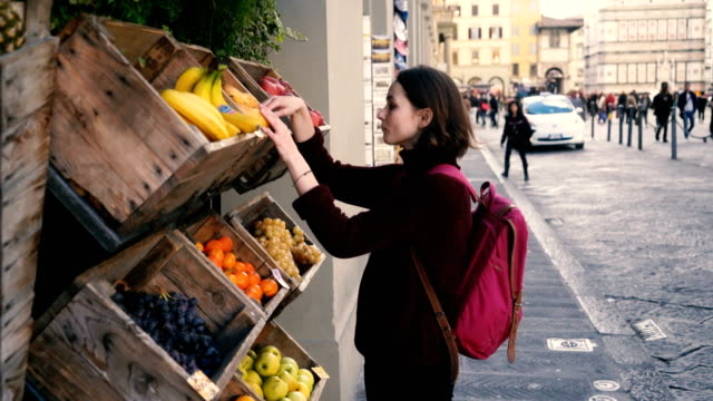 vídeos de stock e filmes b-roll de woman choosing fresh fruits on the street of florence - banca de mercado