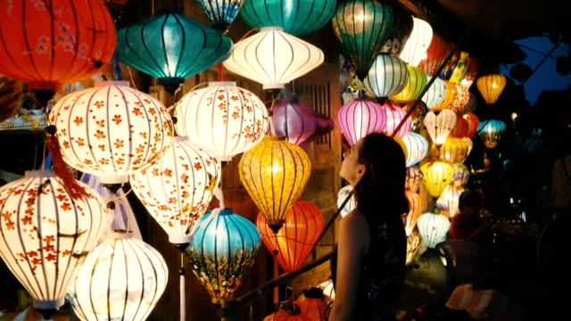 woman choosing lanterns in hoi an - electric lamp video stock e b–roll