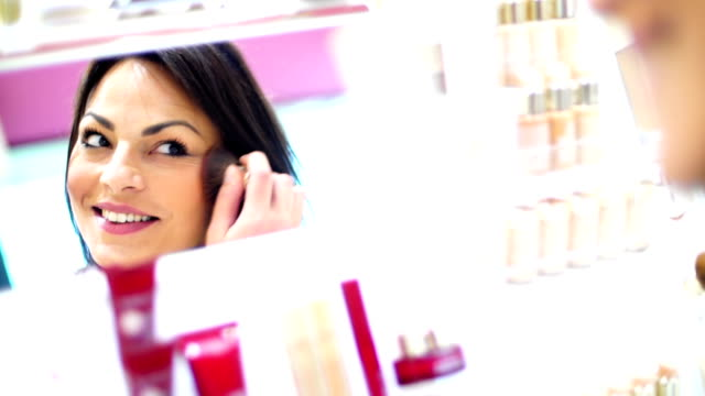 Woman choosing makeup at beauty store.