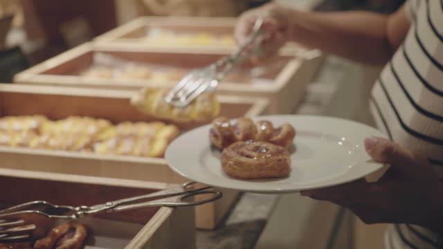 woman choosing pastry for her breakfast - appetiser stock videos & royalty-free footage