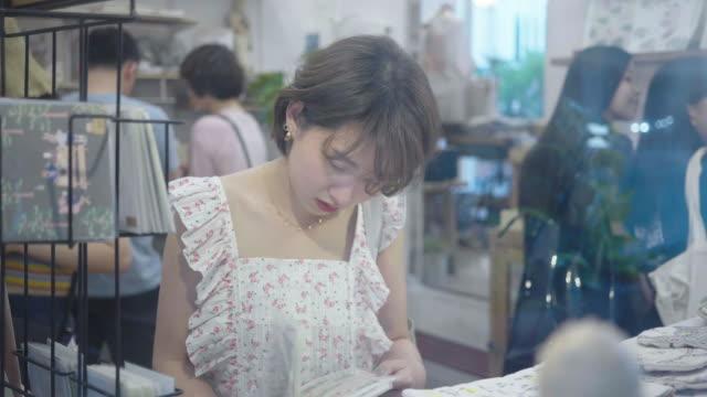 vídeos y material grabado en eventos de stock de mujer eligiendo tarjetas postales en la calle - capital letter