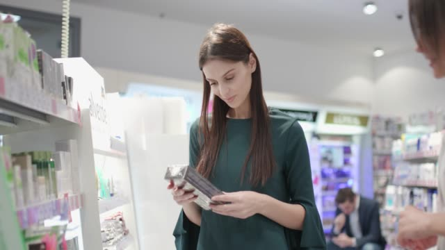 woman choosing skin care product with sales clerk - skin care stock videos & royalty-free footage