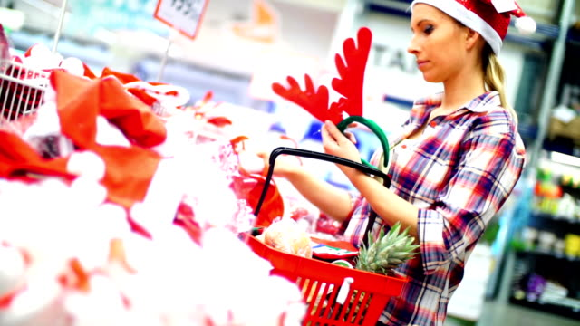 woman choosing some christmas decoration in supermarket. - shopping basket stock videos and b-roll footage