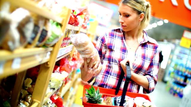 vídeos de stock e filmes b-roll de mulher escolher alguns alimentos no supermercado. - etiqueta mensagem