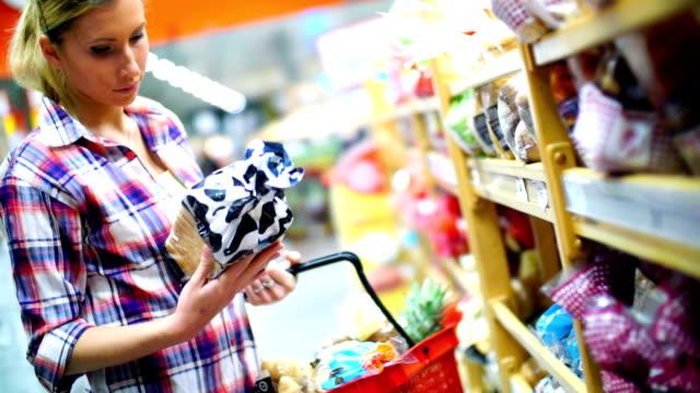 vídeos de stock, filmes e b-roll de mulher escolher alguns alimentos no supermercado. - etiqueta mensagem