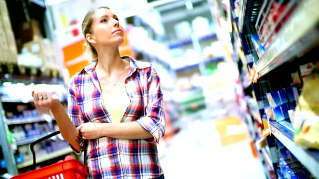 woman choosing some food in supermarket. - shopping basket stock videos and b-roll footage