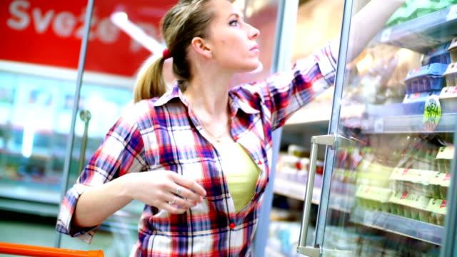 donna in supermercato scegliendo alcuni alimenti. - frigorifero video stock e b–roll