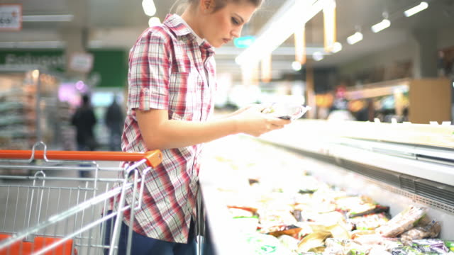 woman choosing some food in supermarket. - packet stock videos and b-roll footage