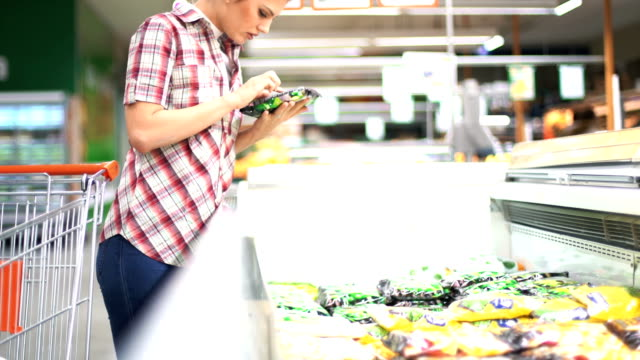 woman choosing some food in supermarket. - packaging stock videos & royalty-free footage