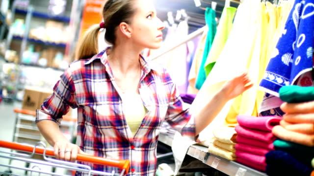 donna scegliere alcuni asciugamani e mops in supermercato. - abbigliamento video stock e b–roll