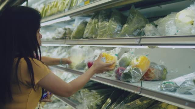 Woman Choosing Vegetables at Supermarket