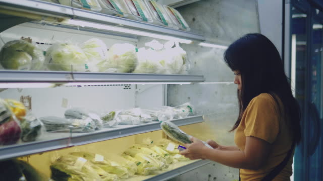 woman choosing vegetables at supermarket - stereotypical homemaker stock videos & royalty-free footage