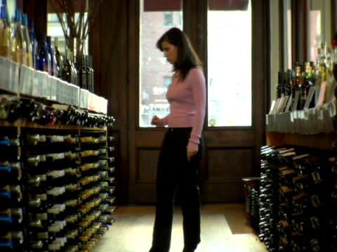 ms, woman choosing wine in liquor store, soho, new york city, new york, usa - crouching stock videos & royalty-free footage