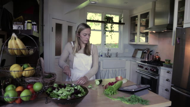 MS Woman chopping cucumbers and placing in salad / Los Angeles, California, United States