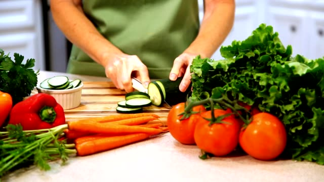 woman chopping vegetables in kitchen. - carving knife stock videos and b-roll footage
