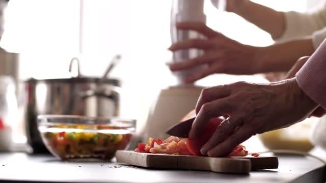frau hackt gemüse auf schneidebrett - essen zubereiten stock-videos und b-roll-filmmaterial