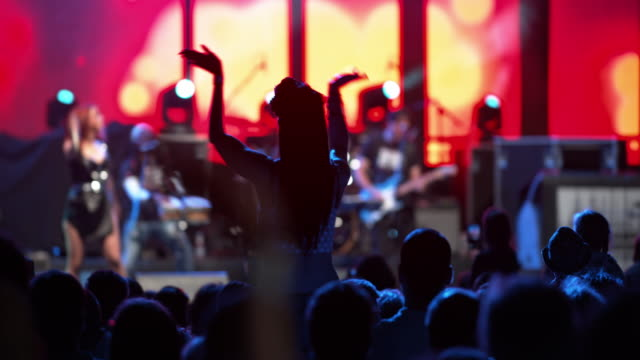 Woman clapping hands on man's shoulders at concert