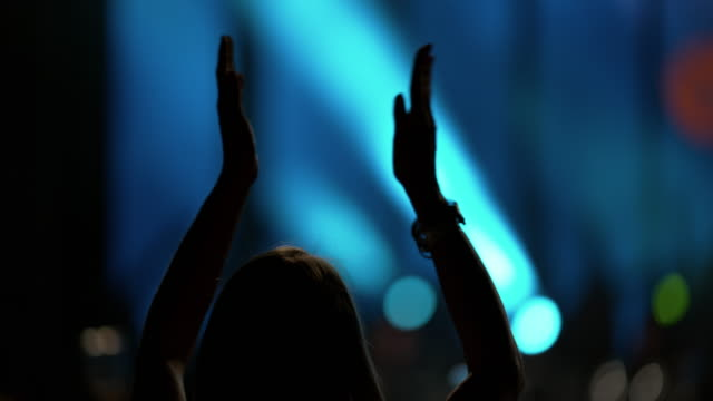 slo mo woman clapping her hands at a night concert - estatico video stock e b–roll