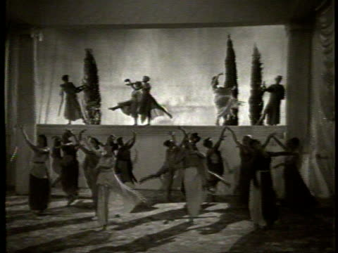 vídeos de stock, filmes e b-roll de a woman claps a slate labeled faust / women dancing in togas behind a white veil / women dressed in grecian clothing dancing in a large room with... - véu