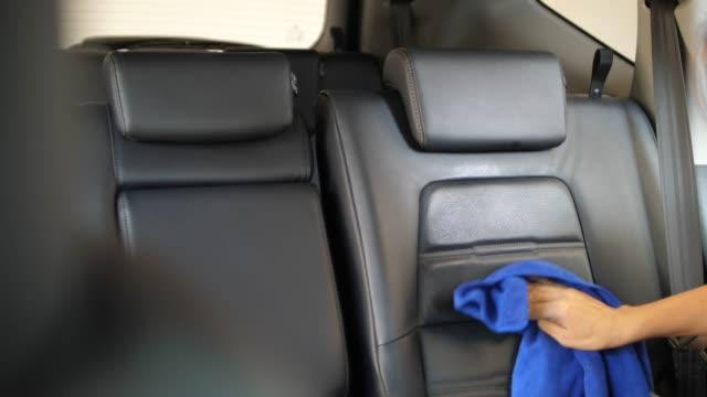 vídeos y material grabado en eventos de stock de mujer limpia su asiento de coche - carrocería
