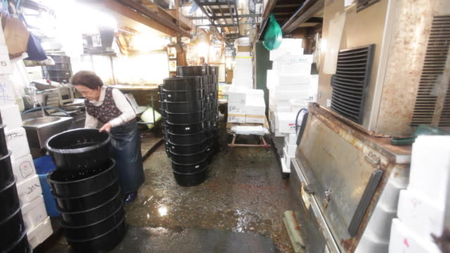 Woman cleaning after busy business day at the Tsukiji Market in Tokyo