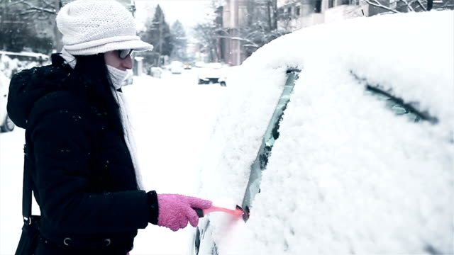 woman cleaning and preparing car for difficult winter drive in the city