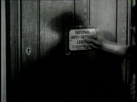 dramatization woman cleaning 'antigambling league 5th door on left' sign on door wiping clean using breath wiping again - 1937 stock-videos und b-roll-filmmaterial