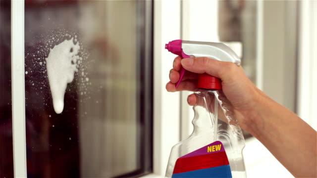 vídeos de stock, filmes e b-roll de mulher limpando grande janela em um dia ensolarado. - pulverizando
