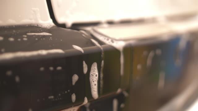 stockvideo's en b-roll-footage met slo mo vrouw schoonmaak auto met spons - foam hand