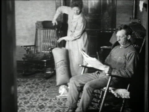 vidéos et rushes de b/w 1925 woman cleaning carpet with early vacuum cleaner near man sitting in chair reading newspaper - faire le ménage