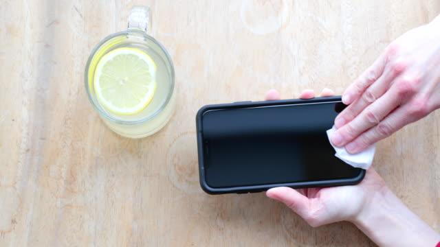 帶抗菌白色紙巾或一次性濕巾的智慧手機清潔顯示幕 - 乾淨 個影片檔及 b 捲影像