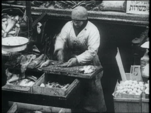b/w 1932 woman cleaning fish at stand on sidewalk as customer approaches / lower east side, nyc - lower east side bildbanksvideor och videomaterial från bakom kulisserna