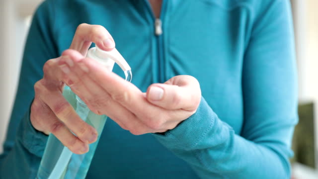 woman cleaning hands with hand sanitizer close up - spingere video stock e b–roll