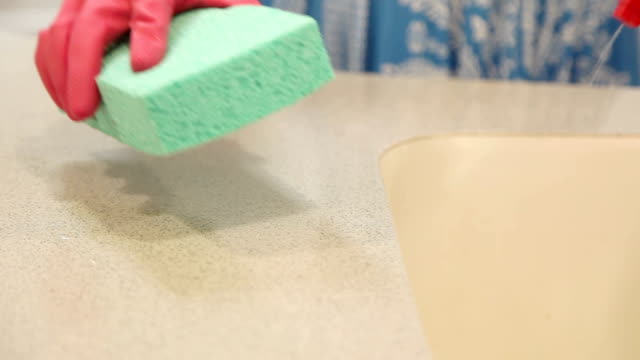 Woman cleaning her home kitchen using sponge, cleaning fluid.