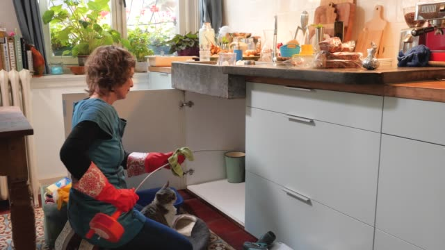 vídeos de stock, filmes e b-roll de woman cleaning her tools after unclogging the drain of the kitchen sink - cabinet