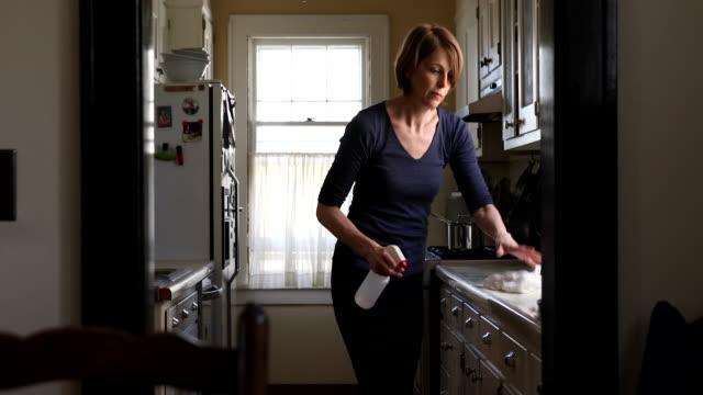 vídeos de stock e filmes b-roll de woman cleaning kitchen counter - banca
