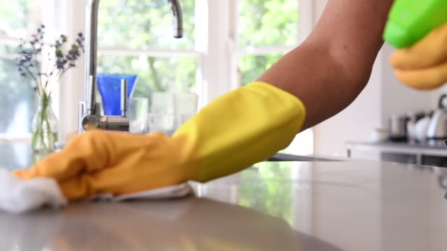woman cleaning kitchen worktop with spray and cloth - pianale da cucina video stock e b–roll