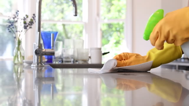 woman cleaning kitchen worktop with spray and cloth - cleaning sponge stock videos & royalty-free footage