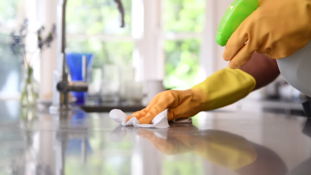woman cleaning kitchen worktop with spray and cloth - spray cleaner stock videos & royalty-free footage