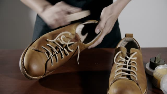 woman cleaning leather shoes at home - animal skin stock videos & royalty-free footage