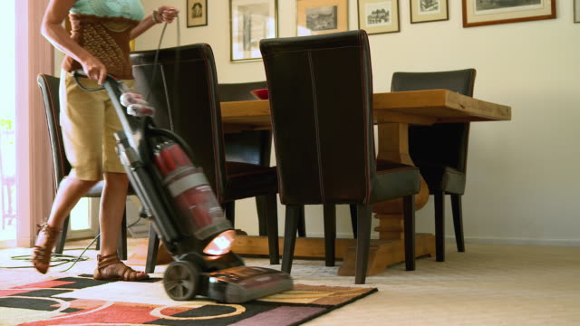 MS  TU TD PAN woman cleaning living room carpet and rugs with upright vacuum cleaner / Rancho Mirage, California, United States