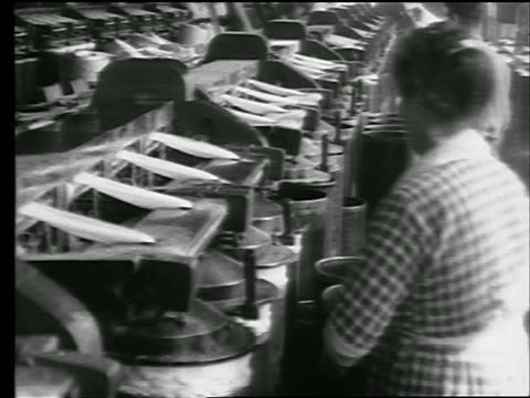 B/W 1922 PROFILE woman cleaning machinery in cotton mill / newsreel