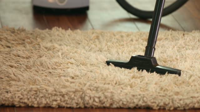 cu pan woman cleaning rug with vacuum cleaner at home / delhi, india - rug stock videos & royalty-free footage