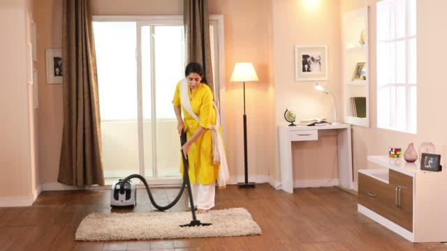 ms woman cleaning rug with vacuum cleaner at home / delhi, india - routine stock videos & royalty-free footage